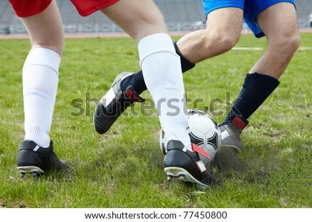 Image of footballers legs kicking soccer ball on stadium - stock photo
