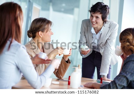 Image of four businesswomen talking about beauty products at break - stock photo