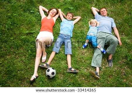 Image of four people lying on the grass together - stock photo