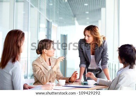 Image of four successful businesswomen interacting at meeting - stock photo
