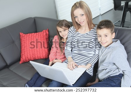Image of friendly family sitting on the sofa and looking at laptop