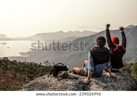 Image of friends who are sitting on top of mountain - stock photo