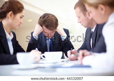 Image of frustrated businessman touching his head while his colleagues looking at him at meeting - stock photo