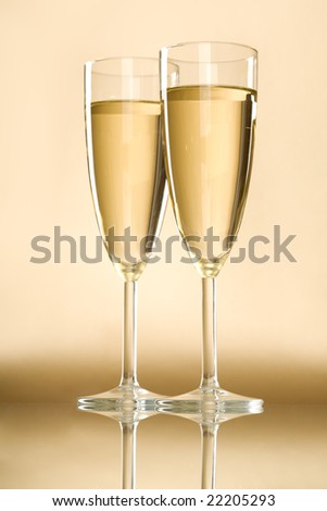 Image of full champagne flutes standing on table with reflection over golden background
