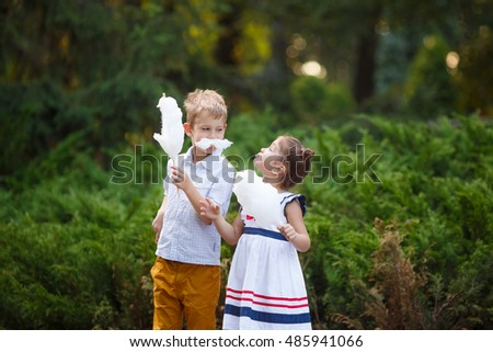 Image of funny chidren with cotton candy posing in the park