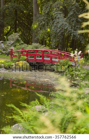 Image of garden pond with japanese style red foot bridge. Krapperup, Sweden.  - stock photo