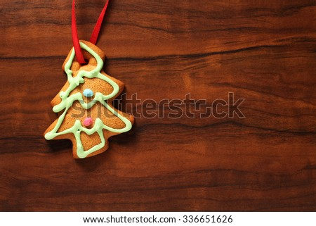 Image of gingerbread Christmas tree cookie over brown wooden texture - stock photo