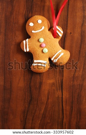 Image of Gingerbread man cookie over brown wooden texture - stock photo