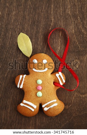 Image of Gingerbread man on brown cutting board - stock photo