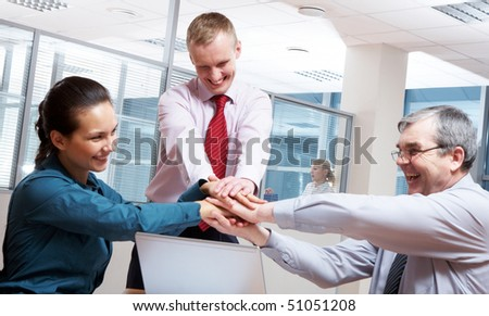 Image of glad businesspeople making pile of hands at meeting
