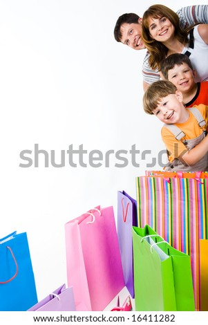 Image of glad family looking at camera with smiles with bags in front of them - stock photo