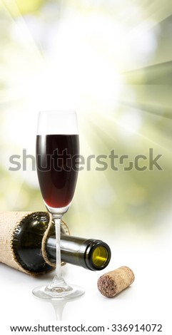 image of glass of wine and  bottle on rays background