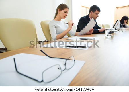 Image of glasses with paper placed on the table on the background of people - stock photo