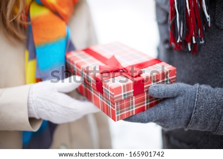 Image of gloved hand of guy giving his girlfriend Christmas present - stock photo