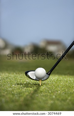 Image of golf ball on tee with golf club behind ball. - stock photo