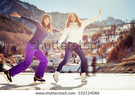 Image of group funny teenagers girls ice skating outdoor at ice rink, posing and looking at camera. Medeo stadium. Almaty. Winter activities for good mood and healthy mind. Healthy lifestyle and sport - stock photo