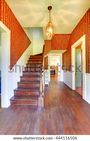Image of Hallway with wooden staircase, red pattern wallpaper and white siding wall trim. - stock photo
