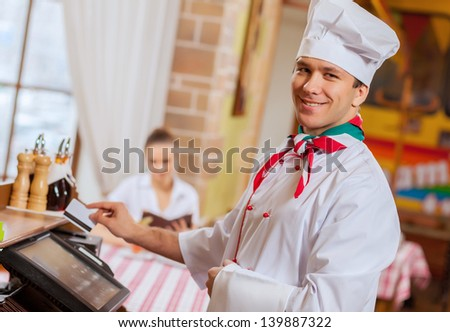 Image of handsome chef inserting card in terminal - stock photo
