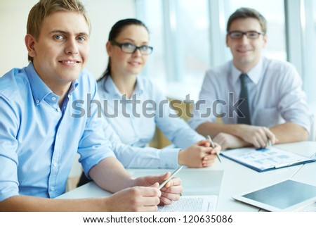 Image of handsome leader looking at camera with two employees behind - stock photo