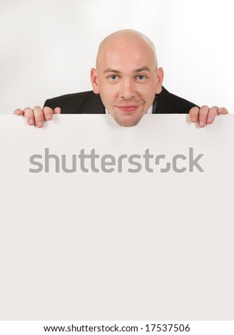 Image of handsome male looking from behind white partition - stock photo