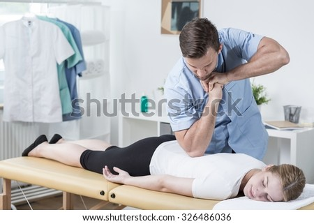 Image of handsome male physiotherapist massaging womans back - stock photo