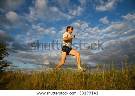 Image of handsome man walking over grass - stock photo