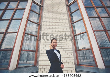 Image of happy businesswoman speaking on the phone outdoors - stock photo