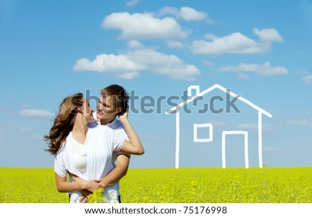 Image of happy couple in yellow meadow with drawn house on background