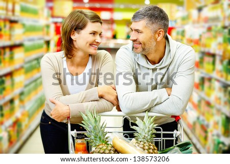 Image of happy couple with cart looking at one another in supermarket - stock photo