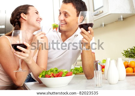 Image of happy couple with glasses of red wine eating salad
