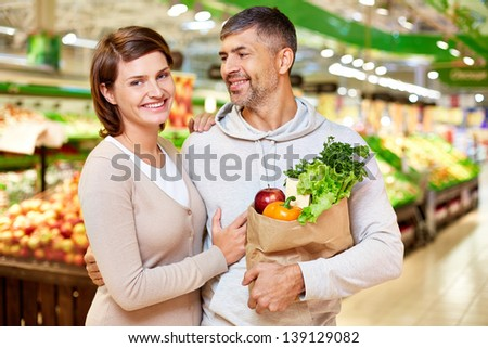 Image of happy couple with paperbag full of products looking at camera in supermarket - stock photo