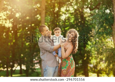 Image of happy family of three people. Father, mother, baby playing outside in summer day at sunset time. Portrait of multiethnic family in park. Arabian daddy and European mom holding child in hands. - stock photo