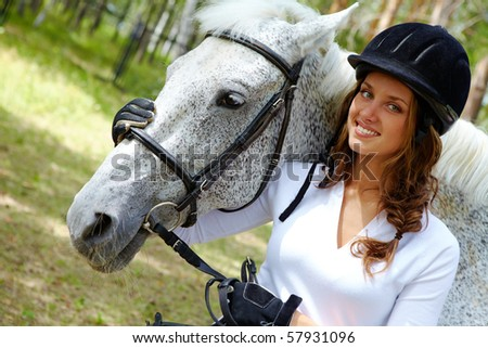 Image of happy female in riding cap embracing purebred horse and looking at camera - stock photo