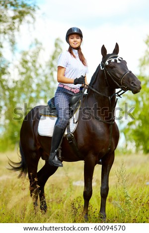 Image of happy female sitting on purebred horse and looking at camera outdoors - stock photo