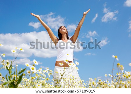 Image of happy female standing with raised arms on summer day - stock photo