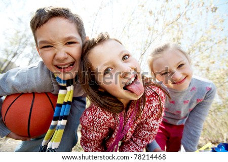 Image of happy friends looking at camera with funny girl showing her tongue in front - stock photo