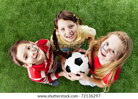 Image of happy friends on the grass with ball looking at camera