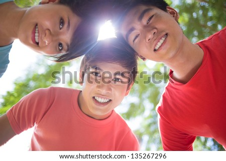 Image of happy friends standing in a circle outside - stock photo