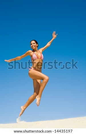 Image of happy girl jumping on sand beach on the background of blue sky in summer