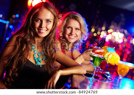Image of happy girl looking at camera with her friend behind