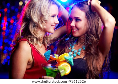 Image of happy girls looking at one another at party