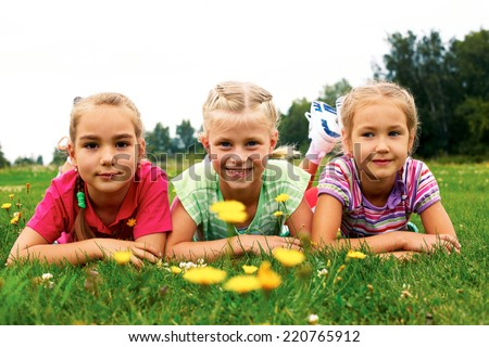 Image of happy group girls lying on a green grass