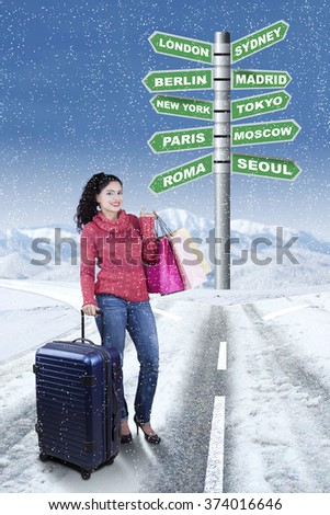 Image of happy Indian woman standing on the road while holding suitcase and shopping bags with road sign of destination city for winter holiday