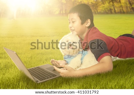Image of happy little boy lying on the grass with his puppy while using laptop computer, shot on the park - stock photo