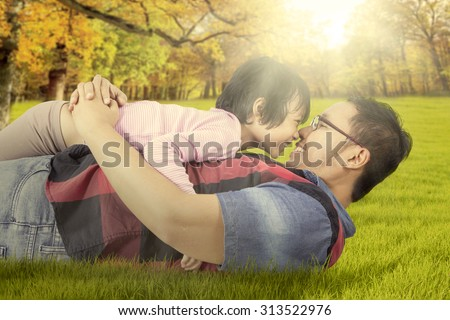 Image of happy little girl playing with her dad on the autumn park while kissing nose to each other - stock photo