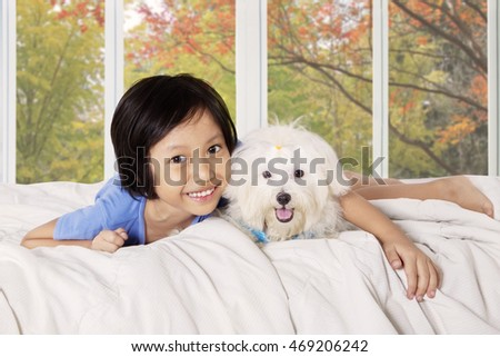 Image of happy little girl smiling at the camera while hugging her puppy and lying on the bed with autumn background on the window