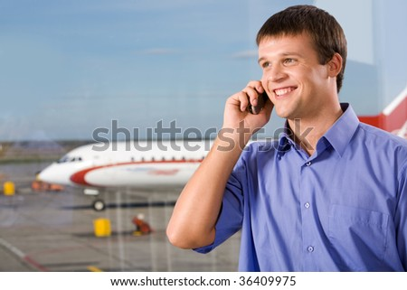 Image of happy male speaking by the mobile phone in airport - stock photo