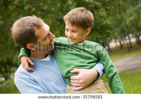 Image of happy man holding his son on hands outside - stock photo