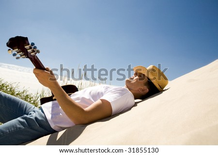 Image of happy man in cowboy hat playing the guitar while relaxing on sandy beach - stock photo