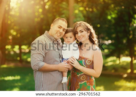 Image of happy mixed races family of three. Father, mother and baby playing outside in summer at sunset time. Portrait of Arabian daddy and European mom holding their child in hands over green trees. - stock photo